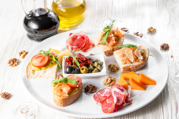 Selection of tasty bruschetta or canapes on taosted baguette and quark cheese topped with smoked salmon, shrimp.