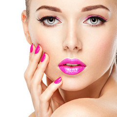 eautiful woman face with pink makeup of eyes and nails.
