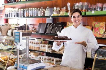 Glad seller offering festive chocolate cake