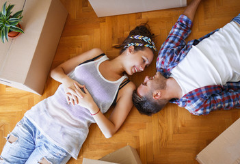 Moving in new home. Couple laying on the floor.