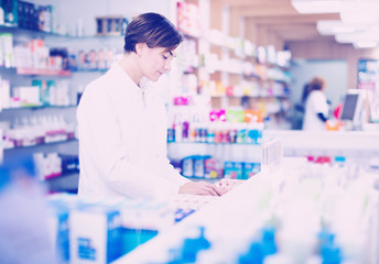 Pharmacist organizing assortment of care products