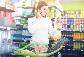 Smiling female talking on phone about shopping
