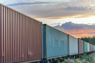 Multicolored railway containers go to the horizon by rail to a beautiful sunset