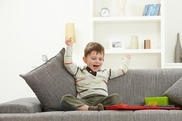 Happy kid with toys sitting on sofa hands in air