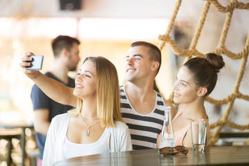 Group of friends taking selfie at bar