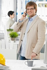 Happy architect at office talking on mobile phone