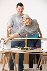 Happy couple renovating painting new home