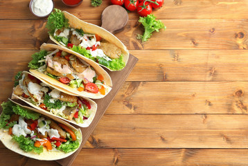 Wooden board with tasty fish tacos on table