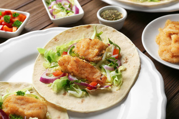 Plate with fish tacos on wooden table
