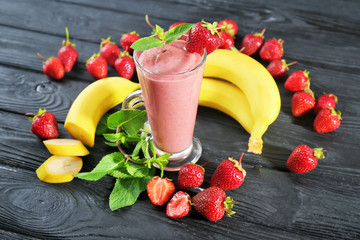 Glass of fresh strawberry and banana smoothie on wooden table