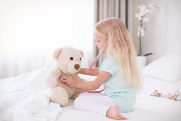 Little girl playing with teddy bear and stethoscope on bed