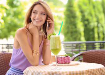Beautiful young woman with fresh smoothie talking on mobile phone in cafe