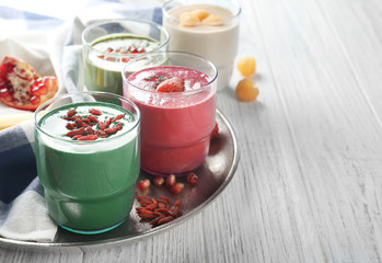 Glasses with different smoothies on metal tray
