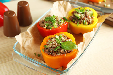Quinoa stuffed peppers in glass baking dish on kitchen table