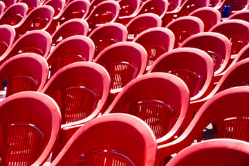Bright empty plastic chairs stand in a row. The place of audience expectations.