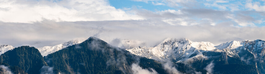panoramic view of the mountains near Chur in the Alps in Switzerland after snow fall and with cloudy sky