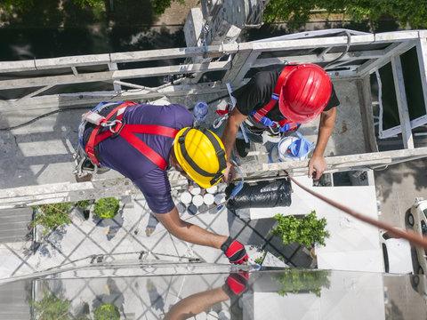 workmen on a suspended platform or cage