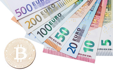 Close up of golden bitcoin and euros on white background, macro shot.