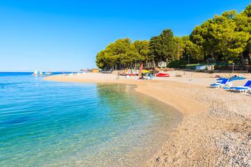 Pebble stone beach with crystal clear azure sea water in Primosten town, Dalmatia, Croatia