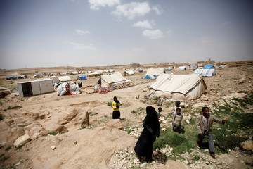 People stand near a tent at a camp for people displaced by the war in Khamir area of the northwestern province of Amran