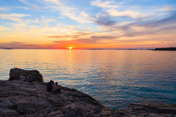 Unidentified couple of people sitting on rocks and watching sunset in Primosten town, Dalmatia, Croatia