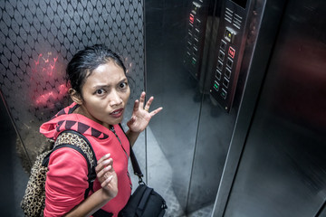 The shocked woman in the moving elevator is watched by a camera. Frightened woman with claustrophobia in an steel lift look into the camera. Horror in the modern lift.