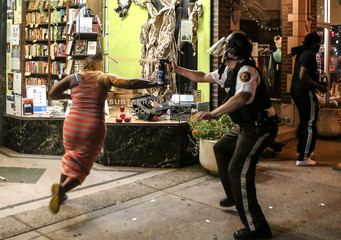 A protester is sprayed with mace by riot police after throwing a chair through a window of a business during the second night of demonstrations after a not guilty verdict in the murder trial of former St. Louis police officer Jason Stockley in St. Louis