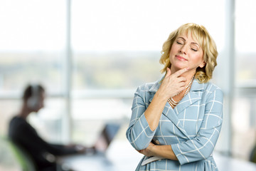 Relaxing woman on office background. Dreaming mature woman closed eyes. Senior woman closed her eyes touching chin on office window background.