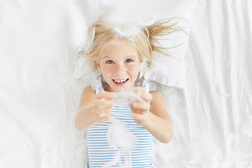 Portrait of playful charming freckled little baby child plays with feather in bed, has positive expression. Amused child catches feathers, looks happy. Children, happiness and facial emotions