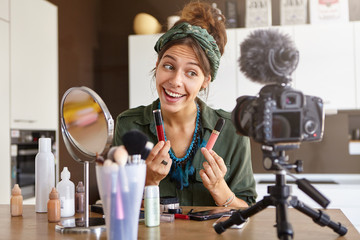 Portrait of excited cheerful young woman vlogger holding two lipsticks of different brands and comparing them, filming make up video review on professional camera. E-commerce, cosmetics and beauty