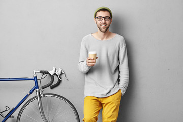 Confident young European male student with beard and mustache smiling broadly having happy look wearing hat and eyeglasses enjoying morning coffee out of papercup before commuting to college Wall mural