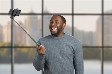 Laughing man taking selfie with monopod. Handsome black guy taking selfie with monopod on blurred background. Excited afro american man with monopod.