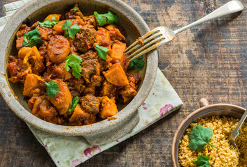 Maroccan lamb tajine with couscous garnished with fresh coriander leaves
