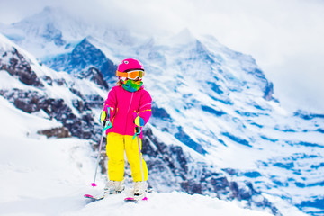 Ski and snow fun. Child in winter mountains.