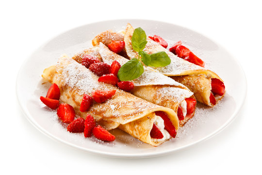 Crepes with strawberries and cream on white background