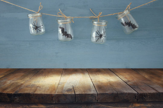 Halloween holiday concept. Empty old wooden table in front of masson jars with spiders and baths decorations