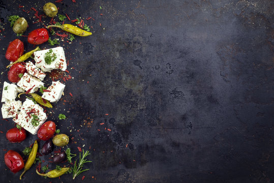 Traditional Greek feta with vegetable and peperoni as top view with copy space right on an old rustic board