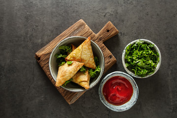 Asian food. Vegetarian samsa with tomato sauce and herbs. Dark background.