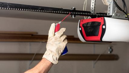 Applying oil to a chain of a garage door opener Wall mural