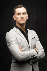 The young man in a gray suit on a dark background.