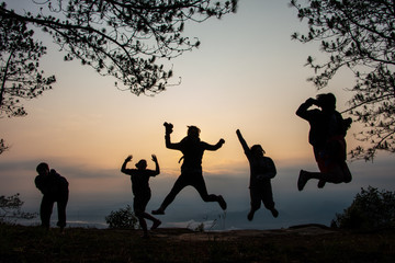 Group of friends enjoy jumping photography at sunrise time.