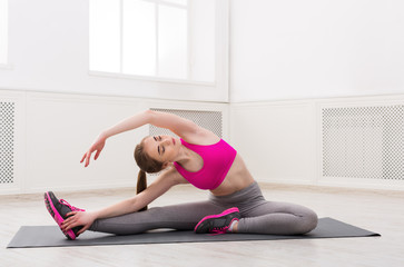Fitness woman stretching at white background indoors