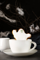 Sweet Halloween. Hot cocoa with cookies in the form of ghosts, leaves and pumpkins. Dark background. Space for text.