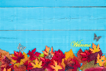 Welcome sign with butterfly on rustic teal blue wood background with colorful autumn leaves border