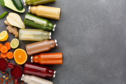 Assortment of detox smoothies in glass bottles on gray background.