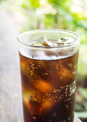 Black soft drink in glass. Garden view with bokeh. Favorite soft drink for refreshment.