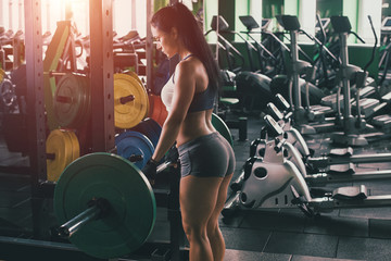 Beautiful athlete woman with barbell in fitness club.