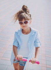 Little girl riding scooter outdoors. Street urban background