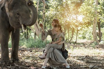 Portrait art of beautiful woman and girl playing with elephants in nature