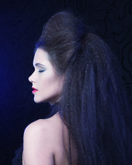 Young brunette woman with high hair and bright make up, gothic